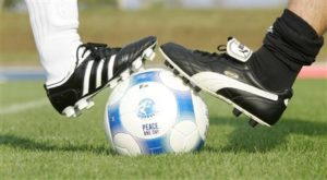 Players wearing Puma and an Adidas soccer shoes pose before a friendly soccer match between German sports goods firm Puma and German sporting goods maker Adidas in Herzogenaurach September 21, 2009. REUTERS/Michaela Rehle